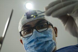 רופא שיניים מסתכל בתוך פה של אישה בהריון