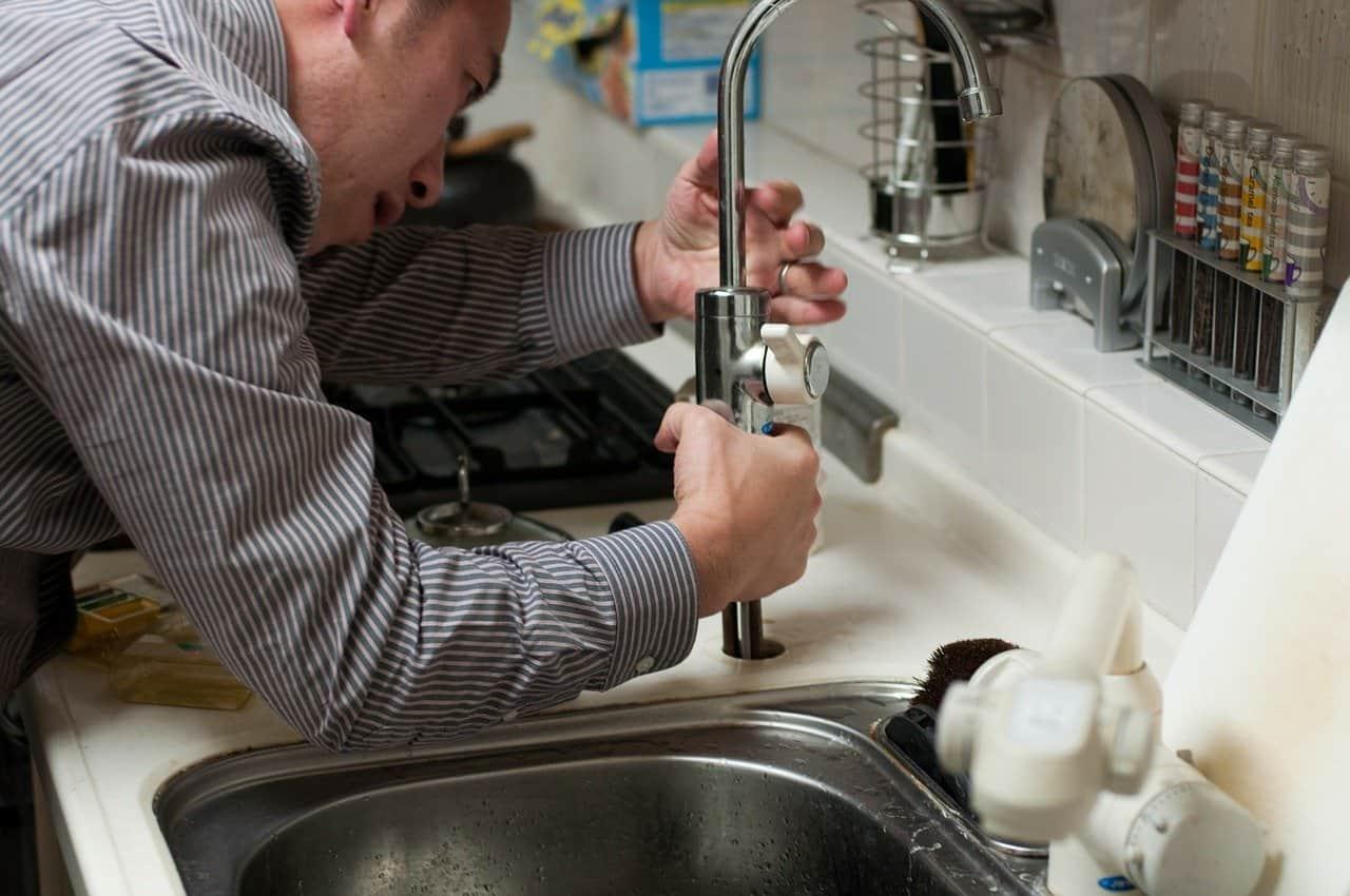 איש רוכן על כיור במטבח ומתקן ברז